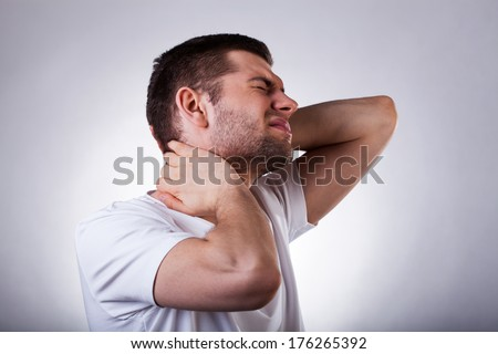 Young exhausted man with strong neck ache isolated on white background - stock photo