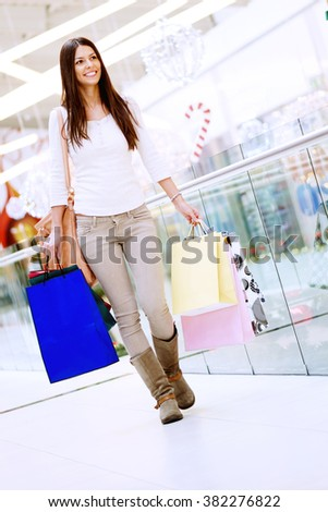 Young exited woman holding shopping bags - stock photo