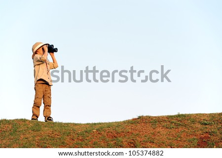 Young explorer looking with binoculars in safari clothing.