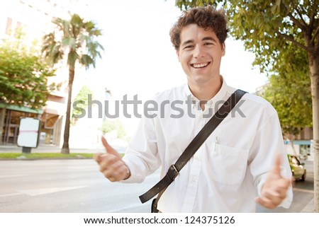 Young expressive businessman standing in a wide city avenue, having a conversation and gesturing with his arms and hands to the camera, outdoors. - stock photo