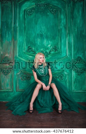 Young extravagant beautiful woman in the studio with hair and professional make-up in green queen vintage dress, bright red lips, blonde, thin waist, beautiful figure, fashion, magazine shooting - stock photo