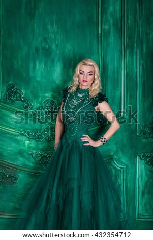 Young extravagant beautiful woman in the studio with hair and professional make-up in green vintage dress, bright red lips, blonde, thin waist, beautiful figure, fashion