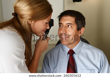 Young eye Doctor during a patient examination in her office - stock photo