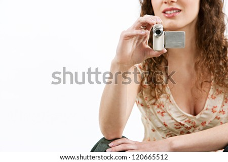 Young faceless woman using a modern silver digital video camera against a white background.