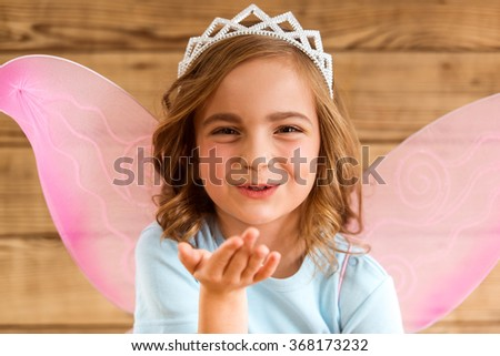 Young fairy with pink wings and white crown on her head sends a kiss against wooden background - stock photo