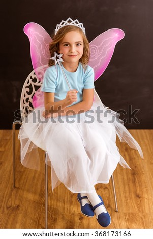 Young fairy with pink wings and white crown on her head sitting in a chair that is on the wooden floor - stock photo