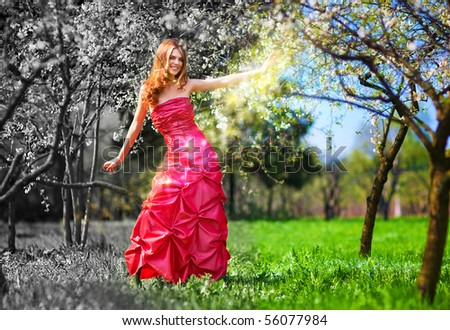 Young fairy woman in red dress painting garden. - stock photo