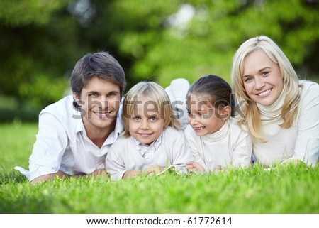 Young families with children lying on the grass in the park - stock photo