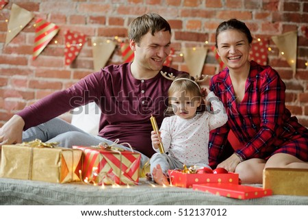 Young family celebrating Christmas. Room is decorated with Christmas lights. Young people have prepared Christmas gifts for each other and little daughter. All are cheerful and happy. Merry Christmas.