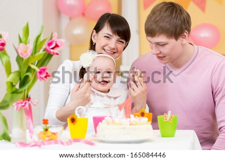 young family celebrating first birthday of baby girl - stock photo
