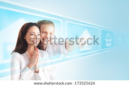 Young family choosing the new home on a virtual touchscreen (real estate, future and technology concept) - stock photo