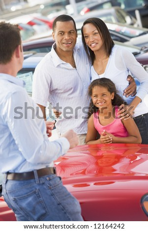 Young family collecting new car from salesman - stock photo