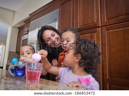 Young Family coloring easter eggs in Kitchen - stock photo