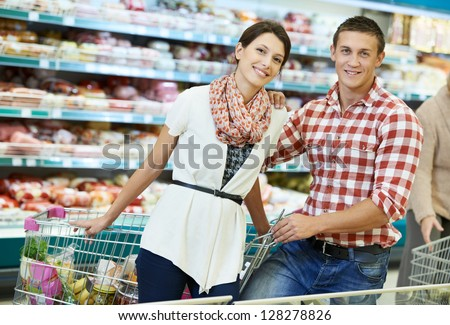 Young Family couple choosing bio food in grocery supermarket during weekly shopping - stock photo