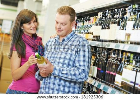 Young family couple choosing bottle ? wine in supermarket during weekly shopping - stock photo