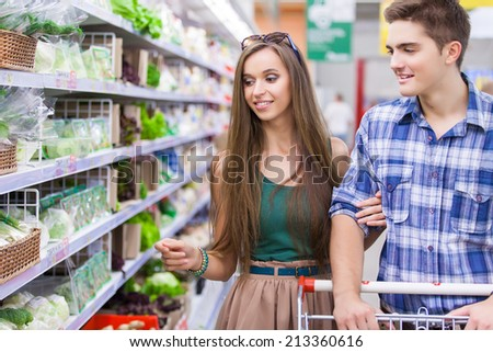 Young Family couple choosing fruit in vegetable supermarket during weekly shopping - stock photo