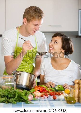 Young family couple cooking vegetables in domestic kitchen