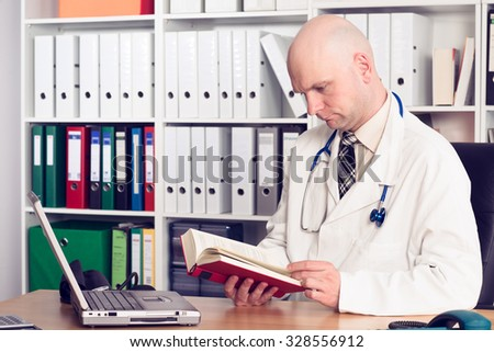 young family doctor in his office  reading a book - stock photo