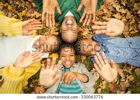 Young family doing a head circles and raising their hands on an autumns day - stock photo
