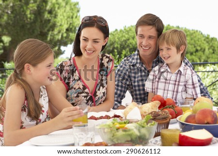 Young Family Enjoying Outdoor Meal Together - stock photo