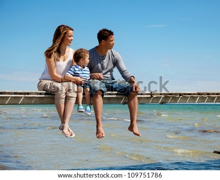 Young family enjoys the beautiful view of the beach - stock photo