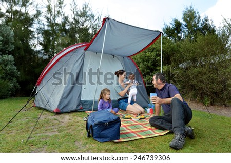 Young family, father and mother with two children camping in a tent outdoors. - stock photo