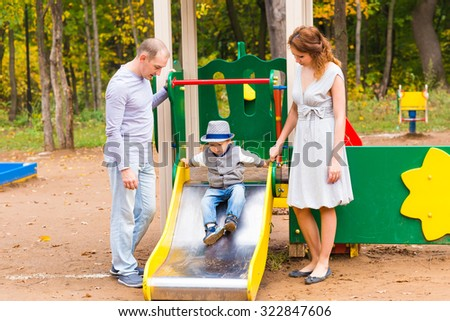 Young family for a walk in a autumn park with baby