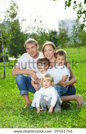 Young family for five persons, has a rest in a summer garden - stock photo