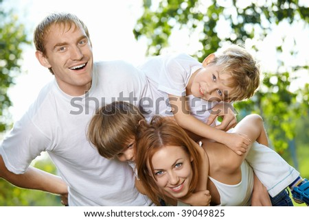 Young family from four members has fun in a summer garden - stock photo