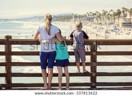 Young family hanging out on an ocean pier on vacation in Southern California - stock photo