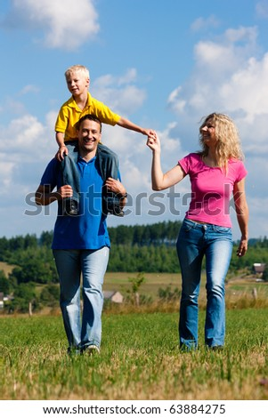 Young family having a walk in the sun over the meadow on a bright summer day - stock photo