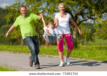 Young family having a walk running on a path and letting the kid fly high - stock photo