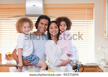 Young family having breakfast in the kitchen - stock photo