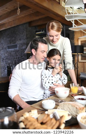 Young family having breakfast together - stock photo