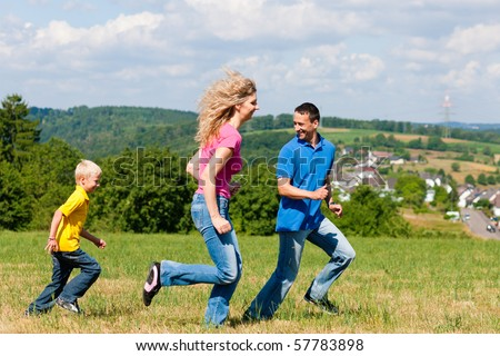 Young family having fun in the sun playing tag on the meadow an a bright summer day - stock photo
