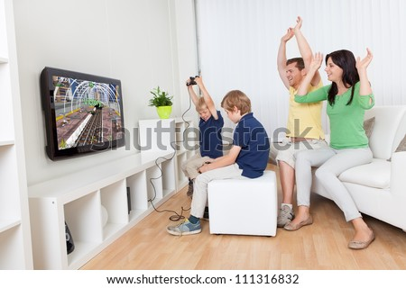 Young family having fun playing videogames at home - stock photo