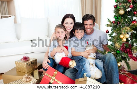 Young family having fun with Christmas presents at home - stock photo