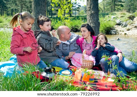 Young family having picnic by the river - stock photo