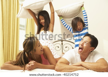 Young Family Having Pillow Fight In Bedroom - stock photo