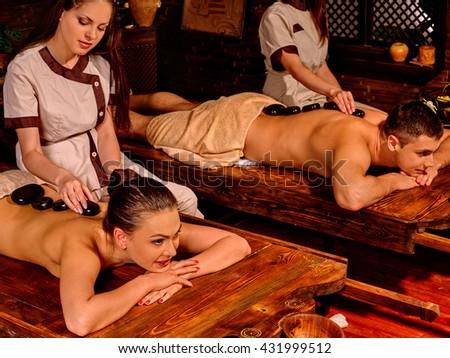 Young family having stone massage. Ayurveda lastone spa massage treatment. - stock photo