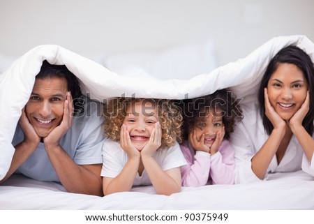 Young family hiding under the blanket
