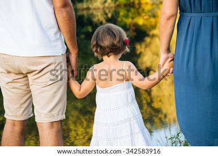 Young family holding hands on the shores of a river. Back view. - stock photo