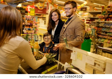 Young family in a grocery store - stock photo