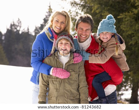 Young Family  In Alpine Snow Scene - stock photo