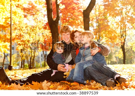 Young family in autumn park lying on yellow leaves - stock photo