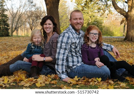 young family in fall leaves