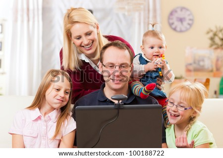 Young family in front of computer with camera having a video chat - stock photo