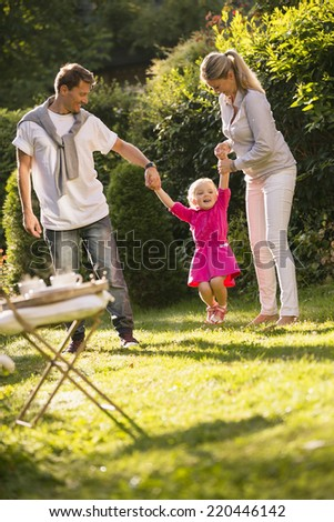 Young family in garden holding hands lifting daughter together - stock photo