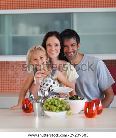Young family in kitchen smiling at camera