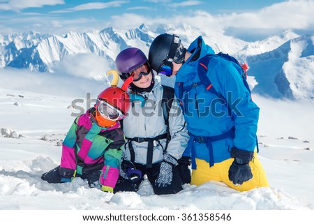 Young family in ski outfit and protective helmets high in the mountains - stock photo